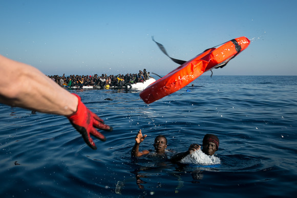 Ein Crewmitglied der Sea-Watch wirft zwei Schiffbrüchigen eine Rettungsweste zu. Foto: Fabian Melber